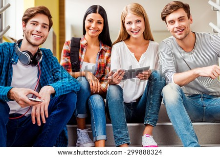 Confident students. Low angle view of four happy young people looking at camera and smiling while sitting on the stairs #299888324