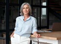 Confident stylish european mature middle aged woman standing at workplace. Stylish older senior businesswoman, 60s gray-haired lady executive leader manager looking at camera in office, portrait.