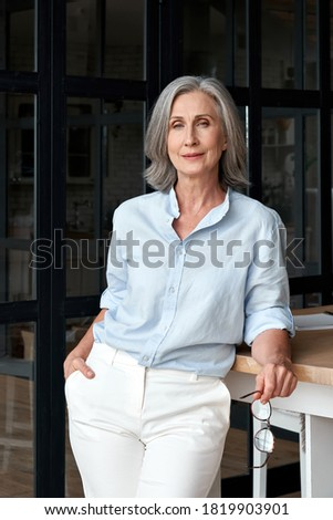 Confident stylish mature middle aged woman standing at workplace. Stylish older senior businesswoman, 60s grey-haired lady executive leader entrepreneur looking at camera in office, vertical portrait.