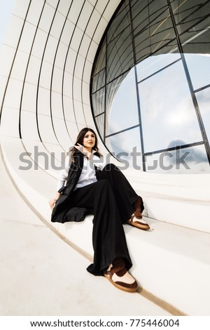 confident stylish woman in a black suit and white shirt posing against the background of an unusual building in the city of Baku