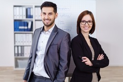 Confident stylish young business partnership with a relaxed man and confident woman with folded arms standing together smiling at the camera