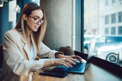 Confident successful female freelancer in non-formal beige baggy suit and spectacles typing on laptop keyboard with enthusiasm while working remotely in urban cafe