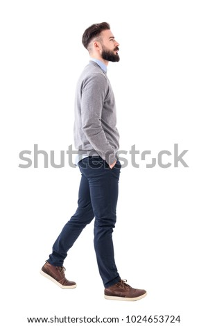 Confident successful smart casual businessman walking with hands in pockets. Full body length portrait isolated on white studio background.