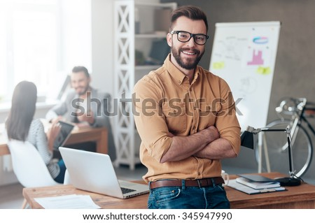 Confident team leader. Confident young man keeping arms crossed and looking at camera with smile while his colleagues working in the background