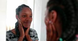 Confident teen adolescent black girl looking herself at mirror