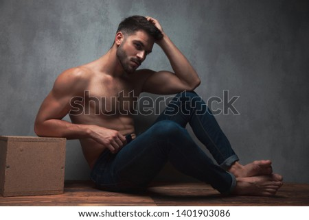 Confident topless young guy holding one of his hands on his head and leaning on a box while sitting on gray studio background