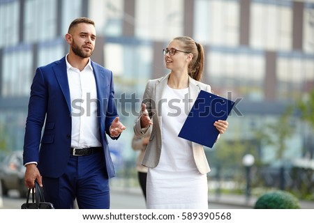 Confident trader explaining something to his colleague while coming back from work