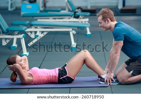 Confident trainer. Concentrated young beautiful woman in sports clothing doing abdominals on the bench in the gym with her sports trainer