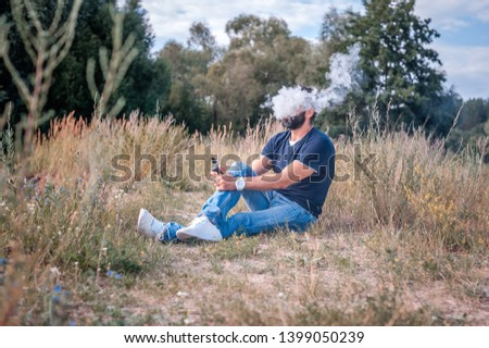 Confident vape man blows up a couple an electronic cigarette. Electronic cigarette as alternative to tobacco. #1399050239
