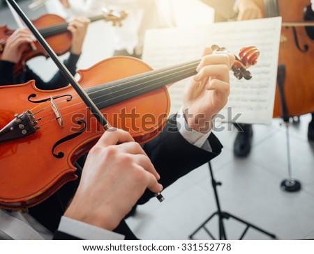 Confident violinist playing his instrument and reading a music sheet, classical music symphony orchestra performing on background