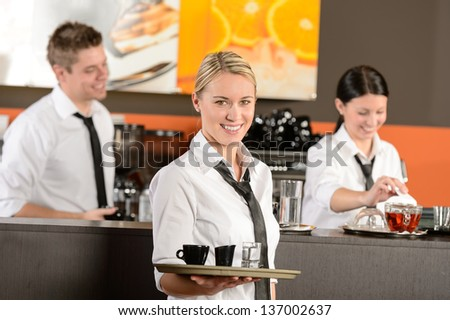 Confident waitress serving coffee with tray colleagues working behind