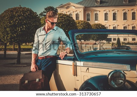 Confident wealthy young man with briefcase near classic convertible  Stock photo ©