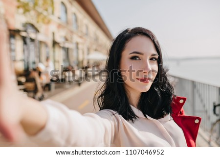 Confident white woman with black hair making selfie with interested face expression. Outdoor photo of enthusiastic young lady wears blouse walking down the street.