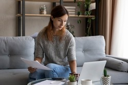 Confident woman calculating expenses or domestic bills, checking financial documents, sitting on couch at home, focused young female using laptop and calculator, managing planning household budget