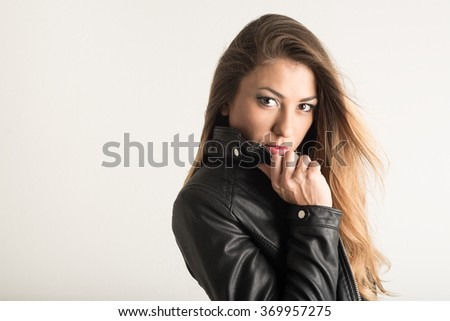 Confident woman close up portrait wearing black leather jacket against white wall background.