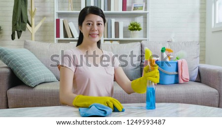 confident woman in rubber protective gloves wiping table holding detergent in the bright living room. beautiful housewife doing housework joyfully indoors in the daytime. lady face camera smiling. #1249593487