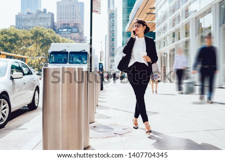 Confident woman in spectacles dressed in elegant suit strolling around modern streets in New York and using 4g internet connection for making international conversation with business partner