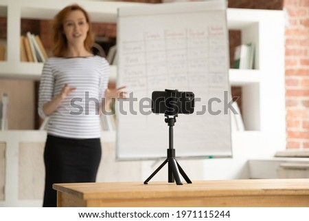 Confident woman mentor recording presentation, webinar on smartphone standing on tripod, teacher coach explaining, holding online lesson, using phone webcam, e-learning and distance education