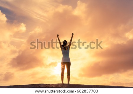 Confident woman raising her hands up in the air. People success, victory, and power.