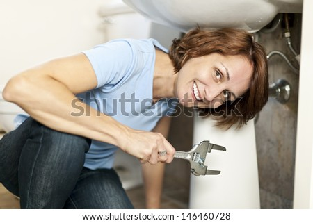 Confident woman repairing sink in bathroom at home