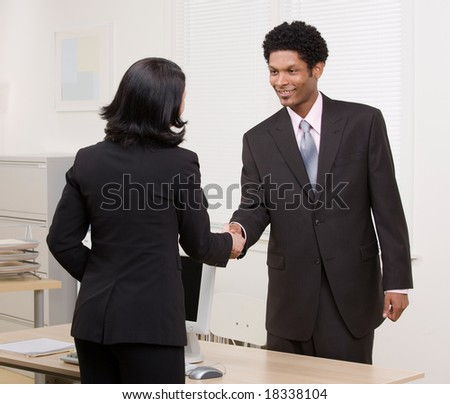 Confident woman shaking hands with co-worker at desk in agreement