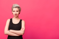 confident woman standing with arms crossed isolated over pink background
