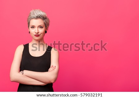 confident woman standing with arms crossed isolated over pink background #579032191