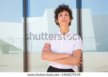 Confident woman standing with crossed arms. Beautiful middle aged businesswoman standing with crossed arms near glass window and looking at camera outdoor. Confidence concept