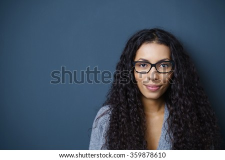 confident woman with glasses looking at camera standing against dark grey background in the studio