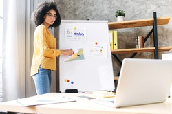 Confident young african-american woman conducts webinar, business training online. Online coach stands near flip chart in front of laptop and explains something to online audience