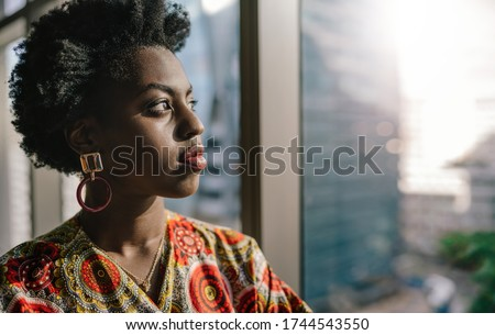 Confident young African businesswoman looking out at the city skyline through an office building window