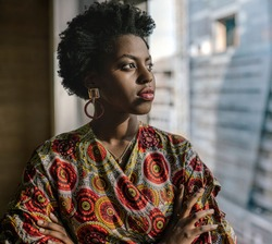 Confident young African businesswoman standing with her arms crossed and looking out at the city through an office window