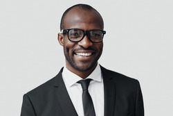 Confident young African man in formalwear looking at camera and smiling while standing against grey background