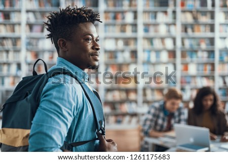 Confident young Afro-American man having backpack on one shoulder and smiling while looking into the distance