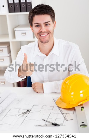 Confident young architect sitting at his desk in his office with a set of rolled blueprints and a hardhat smiling at the camera