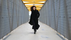 Confident young beautiful female model with tan skin and brown hair fiercely walking along a bridge with cement ground and metal rails on an overcast cold autumn day in a black trench coat