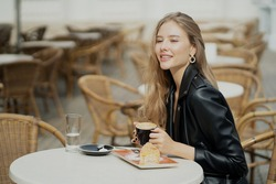 confident young blonde woman. drinks hot flavored delicious cappuccino coffee in a paper Cup. She looks at her friend and smiles.