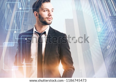 Confident young business leader in black suit looking forward standing in morning city downtown. Hud and gui holograms in the foreground. Hi tech concept. Toned image double exposure copy space #1186745473