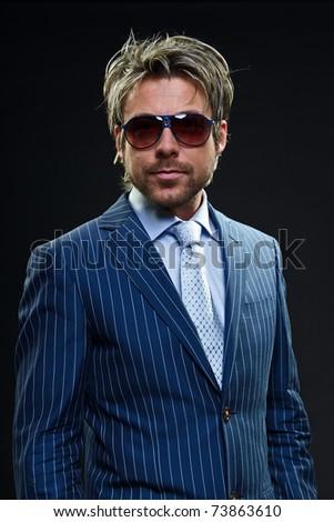 Confident young business man wearing sunglasses in blue striped suit. Self secure. Success. Positive. Power. Summer. Short blond hair. Studio portrait. Black background.