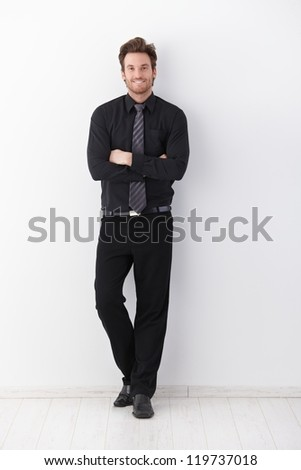 Confident young businessman smiling arms crossed, leaning to wall.