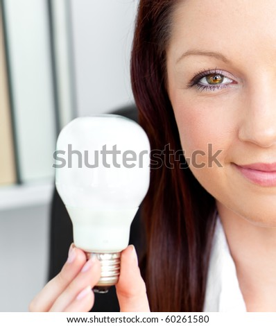 Confident young businesswoman holding a light bulb looking at the camera in her office