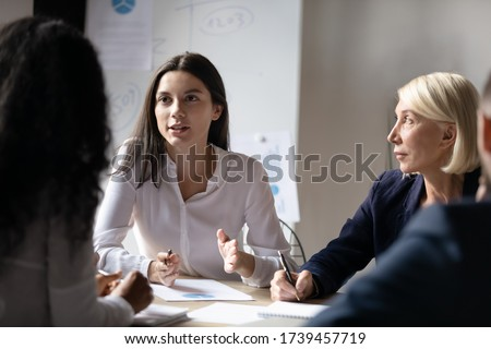 Confident young businesswoman speaking at corporate meeting, female intern sharing startup ideas, discussing project strategy with colleagues at briefing, group business partners negotiation