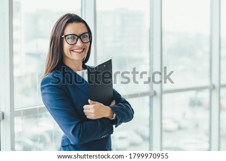 Confident young businesswoman standing with folder in hands, looking at the camera, ready to hard work day. Foto stock ©