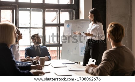 Confident young businesswoman talk make flip chart presentation for diverse businesspeople at meeting, serious female coach or trainer speak present business project on whiteboard at briefing
