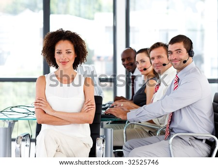 Confident young businesswoman with folded arms in a call center