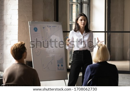 Confident young Caucasian female leader talk make flip chart presentation for diverse employees, serious millennial businesswoman present business project on whiteboard at meeting in office