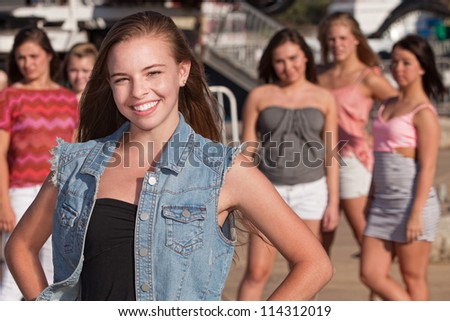 Confident young Caucasian girl in front of jealous friends