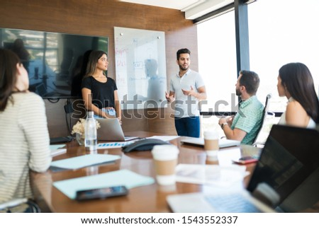 Confident young coworkers explaining strategy to colleagues in meeting room at coworking office