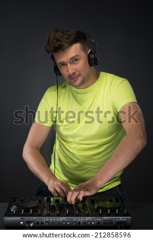 Confident young DJ with stylish haircut and headphones on head mixing music on mixer looking at camera while standing isolated on dark background