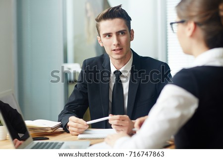 Confident young entrepreneur wearing suit conducting negotiations with female business partner while gathered together at modern boardroom